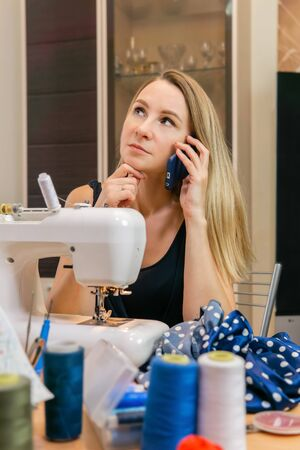 a woman at a sewing machine takes a private order, talking on the phone