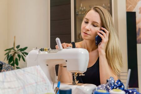 female fashion designer talking on the phone at the sewing machine Reklamní fotografie
