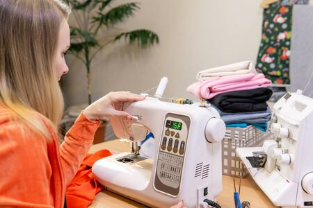 seamstress adjusts the speed of a home sewing machine