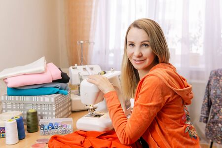 woman seamstress with her equipment at home smiling, looking in frame