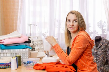 woman seamstress with her equipment at home, looking in frame Reklamní fotografie