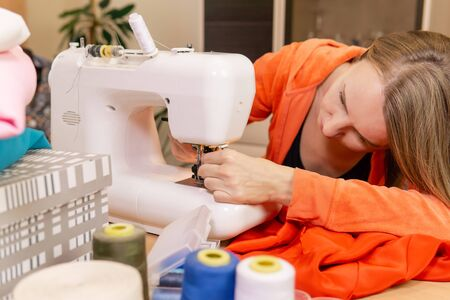 woman tailor is trying to independently install a needle in a sewing machine Reklamní fotografie