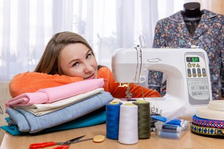 seamstress woman next to her equipment and sewing accessories