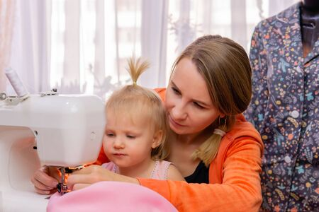 woman sews at home and shows her work to her little daughter
