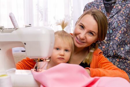 woman is engaged with her daughter interrupting work on a sewing machine Reklamní fotografie