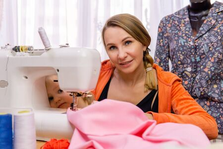 woman is playing with her daughter interrupting work on a sewing machine Reklamní fotografie