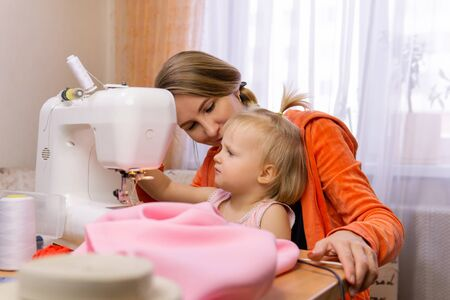 woman sews at home on an electric sewing machine and engages with her small daughter