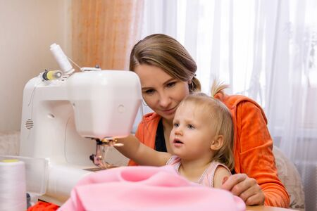 woman sews at home on an electric sewing machine and engages with her toddler daughter