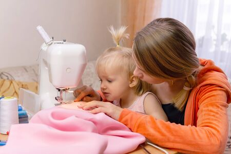 woman sews at home and shows her work to her small child Reklamní fotografie