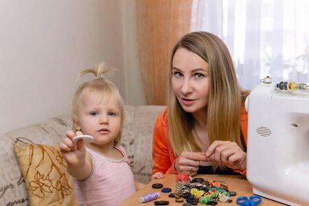 mother while working at home communicates with a small daughter, sorting through buttons