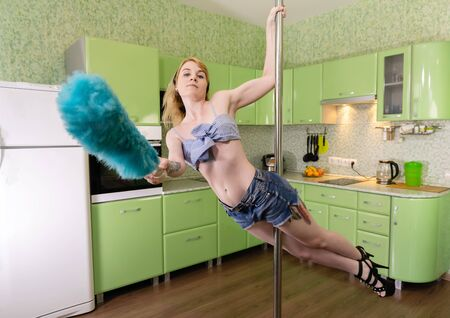 young woman trains pole dance skills while cleaning in her studio apartment Reklamní fotografie
