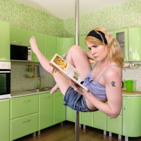 young woman reads a cookbook, exercising in a pole dance in her studio apartment in the background of the kitchen (hieroglyph tattoo means love in Japanese)