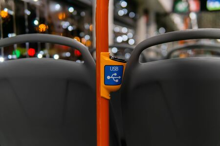 interior elements of public transport - USB port for recharging mobile phones - on a blurred background