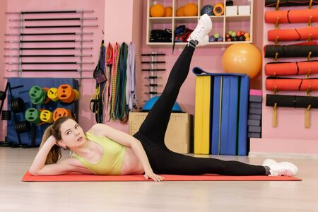 thin young woman who has recently started exercising is engaged in the gym, does a side lying leg lift