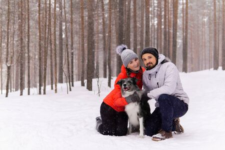 young couple with a dog in a snowy winter forest