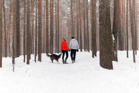 young couple walking a dog in a snowy winter forest, the dog wants to play