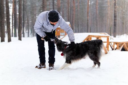 young man plays with a dog in a dog park in a winter forest during a snowfall