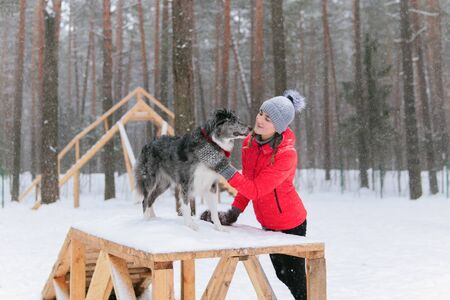young woman encourages her dog standing on a sports equipment in a winter dog park