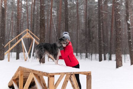 young woman hugs her dog standing on a sports equipment in a winter dog park