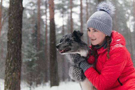 young woman wits her dog in a winter park during snowfall
