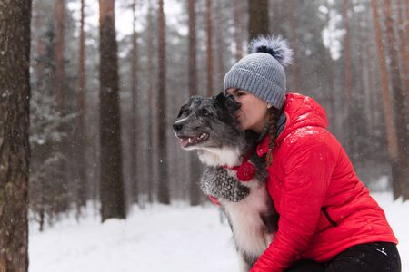 young woman kisses her dog in a winter park during snowfall
