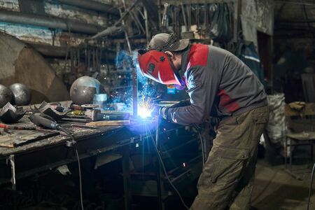 welder works in a small cluttered private workshop Banque d'images