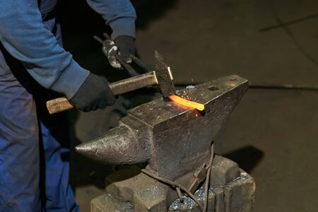 traditional forging of a hot metal billet on the anvil