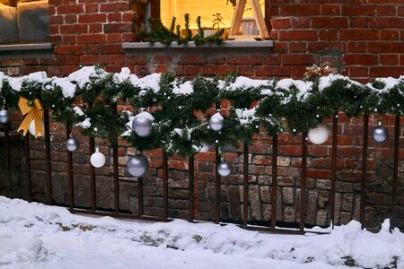 Fencing of semi-basement windows in a vintage building, decorated with snow covered Christmas decorations.