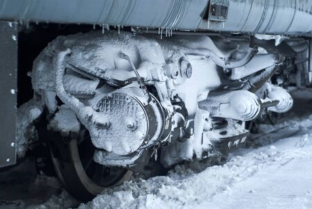 ice and snow covered bogie of a railway passenger carriage on rails during operation in winter
