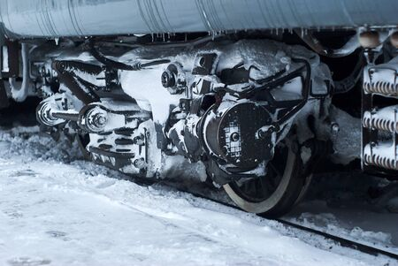 ice and snow covered bogie of a railway passenger carriage on rails during operation in winter Stock fotó