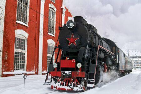vintage steam locomotive passing through train station in winter