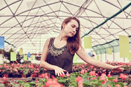 young woman in a dress lovingly touches flowers in a greenhouse