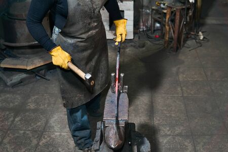 female hands forge a hot metal workpiece on the anvil in a traditional forge Banque d'images