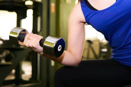 hand of a woman performing dumbbell exercise for biceps at the gym
