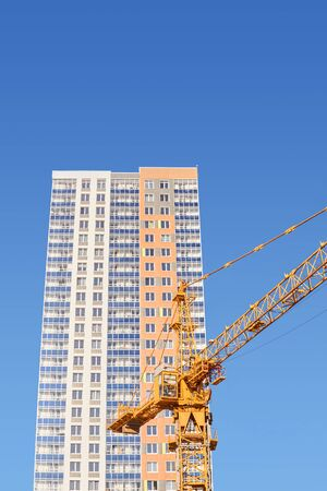 multi-storey construction - cabin and boom of a tower crane and the upper part of a newly-built multi-apartment residential building against the blue sky