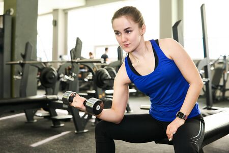 young petite woman performing dumbbell exercise for biceps at the gym in a sitting position