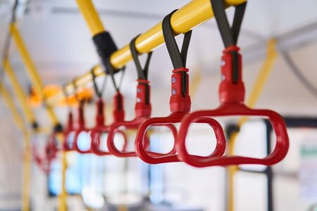 partially blurred row of grab handles for standing passengers in the passenger compartment of the bus close-up Archivio Fotografico