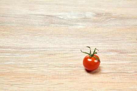 lonely cherry tomato on the edge of a wooden table surface