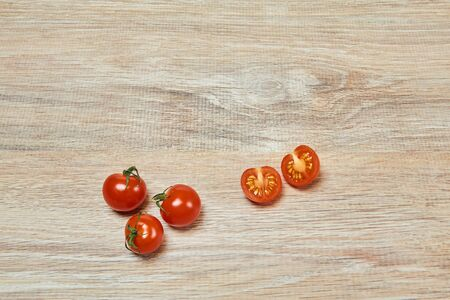 three whole and one cut in half cherry tomatoes on the edge of a wooden table surface Standard-Bild