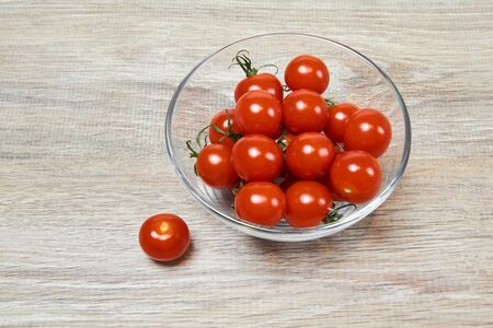 small red cherry tomatoes in a glass bowl and another one near, on a wooden table surface