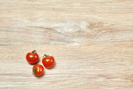 three small cherry tomatoes on the edge of a wooden table surface Standard-Bild
