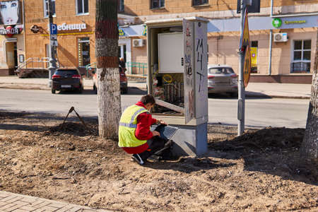 Perm, Russia - April 15, 2020: communications engineer is repairing something in a wired telecommunications network distribution cabinet on a deserted street during quarantine 에디토리얼