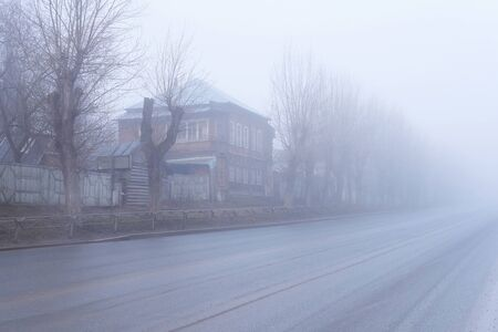 rural asphalt road with wooden houses and roadside fences hiding in a muddy morning fog