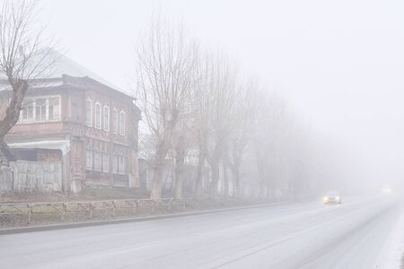 rural asphalt road with wooden houses and roadside fences hiding in a muddy morning fog, the car moving towards is visible