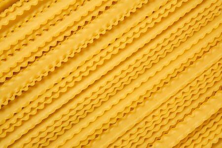 bunch of dry mafaldine pasta on a cane tablecloth 写真素材