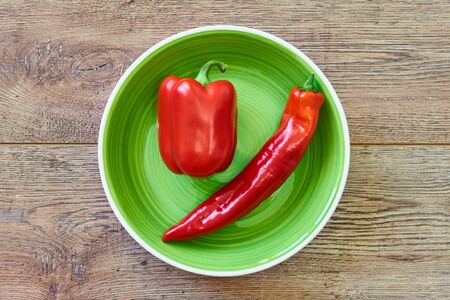 color still life - thin and thick pods of different varieties of sweet pepper on a green plate on a wooden tabletop