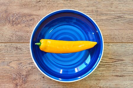 contrast still life - pod of yellow pepper on a blue plate on a wooden tabletop