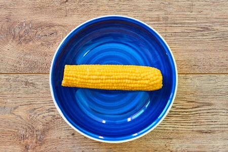 contrast still life - yellow cob of boiled corn on a blue plate on a wooden tabletop