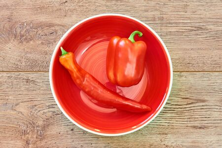 color still life - thin and thick pods of different varieties of sweet pepper on a red plate on a wooden tabletop Archivio Fotografico