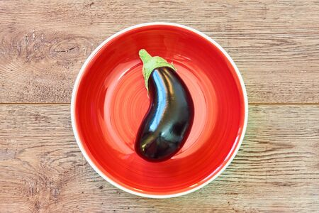 contrast still life - violet, almost black eggplant on a red plate on a wooden tabletop